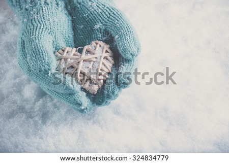 Woman hands in light teal knitted mittens are holding a beautiful heart in a snow background. Love and St. Valentine concept. Instagram effect. - stock photo
