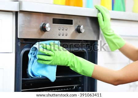 Woman hands in protective gloves cleaning oven with rag - stock photo