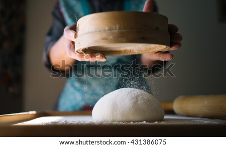 Woman hands knead dough for pasta, ravioli or dumplings. Step by step guide. Closeup, flour flies in air - stock photo