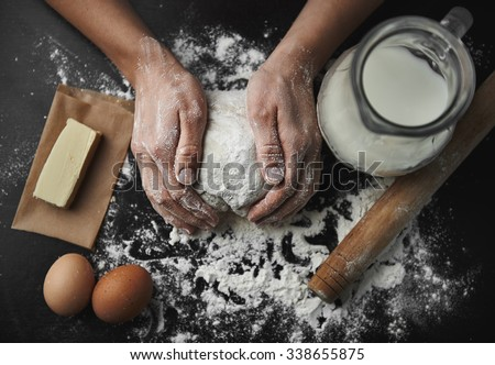Woman hands kneading dough on the black board with eggs, milk, butter and flour. Healthy breakfast preparation concept.  - stock photo