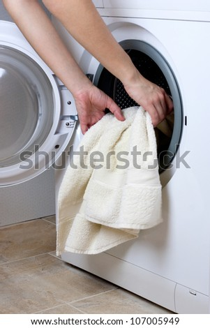 woman hands loading washing machine - stock photo