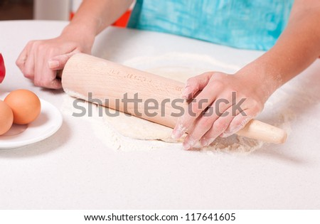 Woman hands mixing dough on the table - stock photo