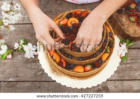 Woman hands of baker carefully decorate cheesecake with fruits and berries on the old planks, white apple and cherry flowers