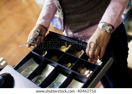 Woman hands on shop cash register. Euro bills and coins. - stock photo