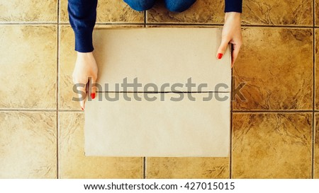 Woman hands opening a parcel contains a gift. Unpacking box with another box. Surprise. Craft present box. People, delivery, shipping service, opening cardboard box or parcel at home. - stock photo