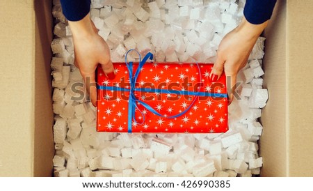 Woman hands opening a parcel contains a gift. Unpacking box with another box. Surprise. Red present box. People, delivery, shipping service, opening cardboard box or parcel at home. - stock photo