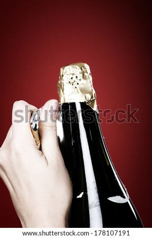 Woman hands opening champagne bottle