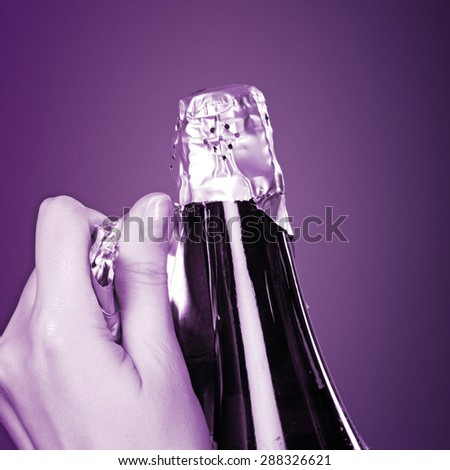 Woman hands opening champagne bottle - stock photo