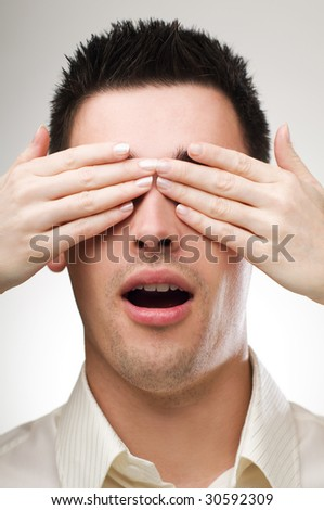 Woman hands over young man eyes close up - stock photo