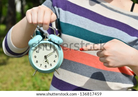 Woman hands pointing on old clock outdoors - stock photo