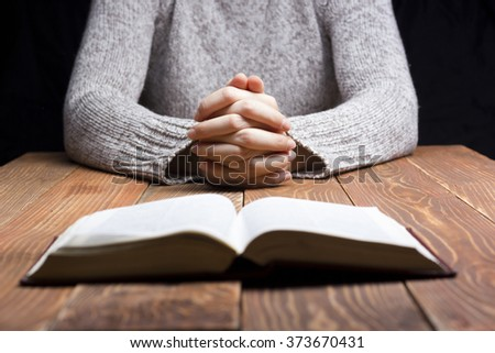 Woman hands praying with a bible in dark over wooden table - stock photo