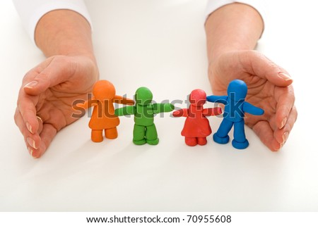 Woman hands protecting colorful clay people - happy family concept - stock photo
