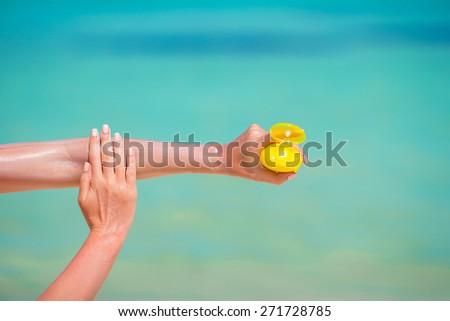 Woman hands putting sunscreen from a suncream bottle - stock photo