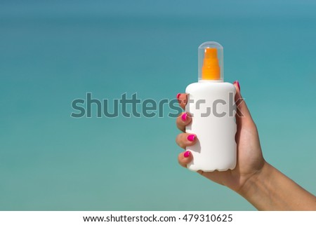 Woman hands putting sunscreen from a suncream bottle