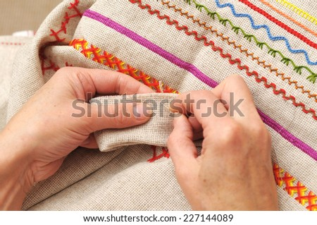 Woman hands sewing with needle and thread - stock photo