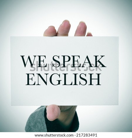 woman hands showing a signboard with the sentence we speak english written in it - stock photo