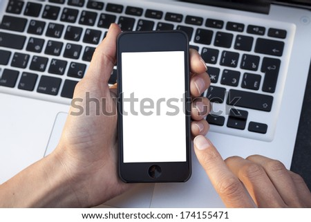 Woman hands showing smartphone white screen with laptop keyboard in background - stock photo