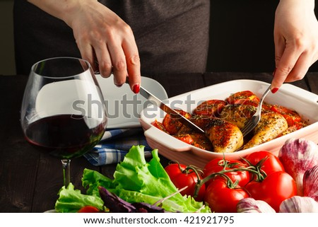 Woman hands slicing up tasty juicy spicy red roasted grilled chicken - stock photo