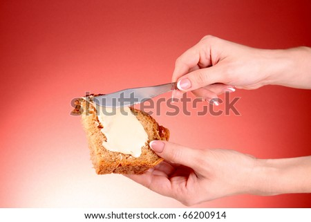 woman hands spread bread with butter on red background