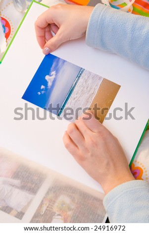 Woman hands sticking images in her photo album. Images can be replaced. - stock photo
