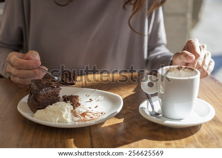 woman hands taking chocolate cake piece with spoon and white small cup cappuccino coffee on light brown wooden table - stock photo