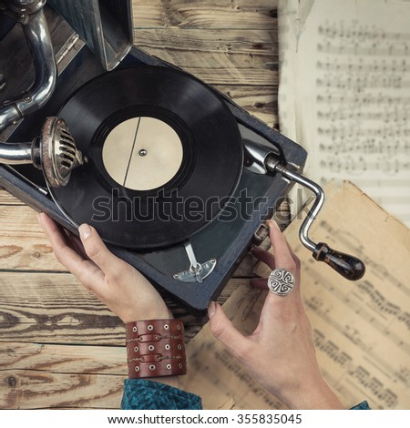 Woman hands touching to the retro gramophone. Cherished memories Rare music things. Toned tinted filtered square photo  instagram retro vintage style - stock photo