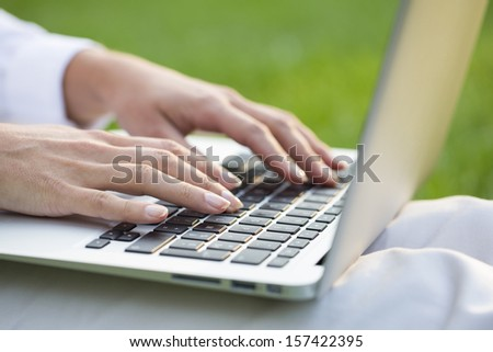 Woman hands typing on a laptop keyboard, outdoor - stock photo