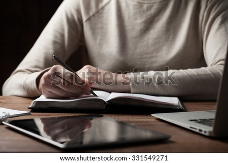 woman hands using laptop and writing at office desk - stock photo
