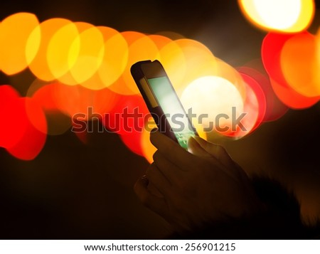 Woman hands using mobile smart phone with glowing screen isolated on street night light with colorful bokeh background  - stock photo