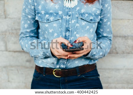 Woman hands using phone against urban concrete wall - stock photo