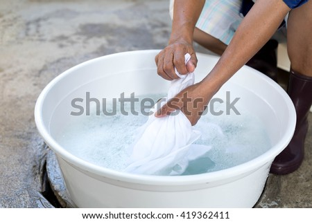 Woman hands wash stain of dirty clothes in big bowl