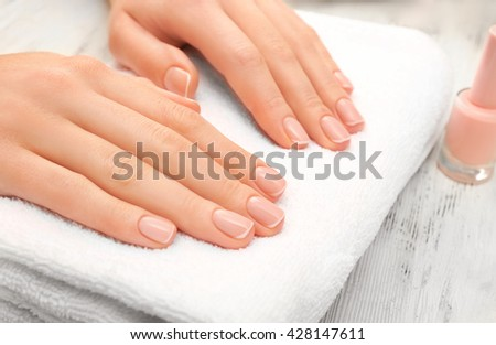 Woman hands with beautiful rose  petals on towel, close up
