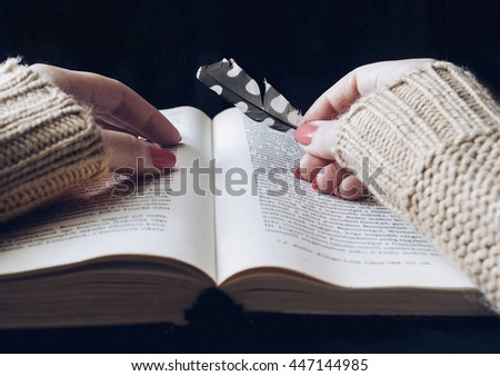 Woman hands with bird feather on a book, filtered photo