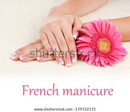 Woman hands with french manicure and flower on towel - stock photo