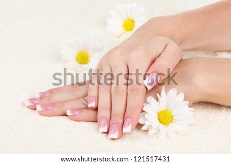 Woman hands with french manicure and flowers on towel - stock photo