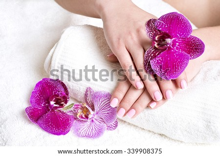 Woman hands with french manicure and orchid flowers on towel - stock photo