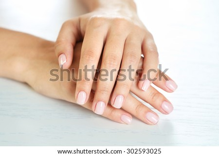 Woman hands with french manicure on table close-up - stock photo