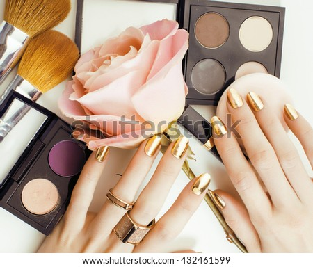 woman hands with golden manicure and many rings holding brushes, makeup artist stuff stylish, pure close up pink flower rose among cosmetic - stock photo
