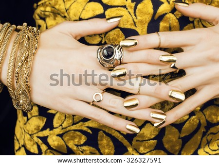 woman hands with golden manicure lot of jewelry on fancy dress close up - stock photo