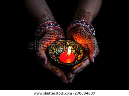 Woman hands with henna holding lit candle isolated on black background with clipping path  - stock photo