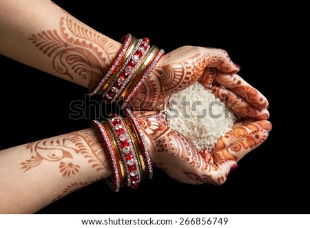 Woman hands with henna holding rice isolated on black background with clipping path