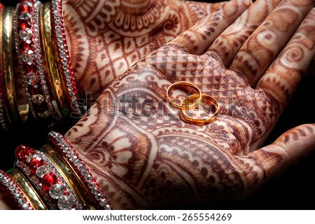 Woman hands with henna holding two golden wedding rings on black background  - stock photo