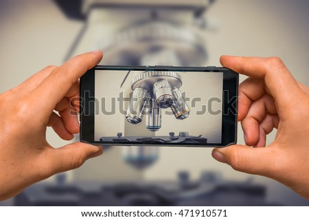 Woman hands with mobile cell phone to take a photo of biological microscope