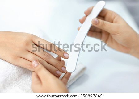 Woman Hands With Nail File. Closeup Of Manicurist Hand Filing Healthy Female Nails With Professional Nail Care Tool In Beauty Salon. Woman Hands With Natural Manicure Polishing Nails. High Resolution