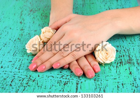 Woman hands with pink manicure and flowers, on color background - stock photo