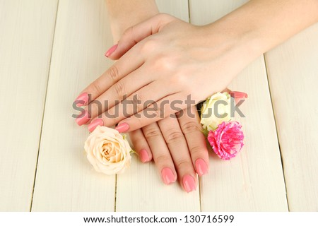 Woman hands with pink manicure and flowers, on wooden background