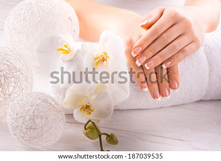 Woman hands with white orchid on a towel - stock photo