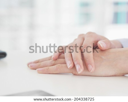 Woman hands with woman hands resting table - stock photo