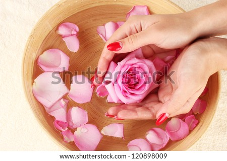 woman hands with wooden bowl of water with petals