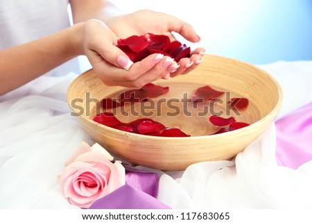 woman hands with wooden bowl of water with petals, on blue background - stock photo